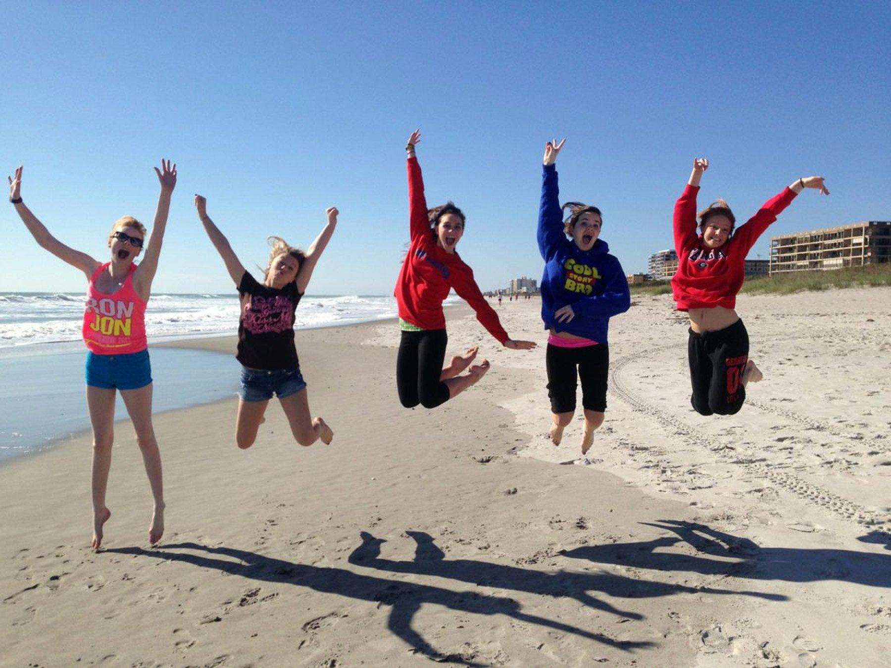 Jeunes filles sautant sur une plage en Floride