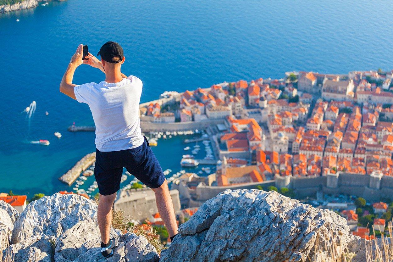 Jeune qui prend une photo sur les hauteurs de Dubronik