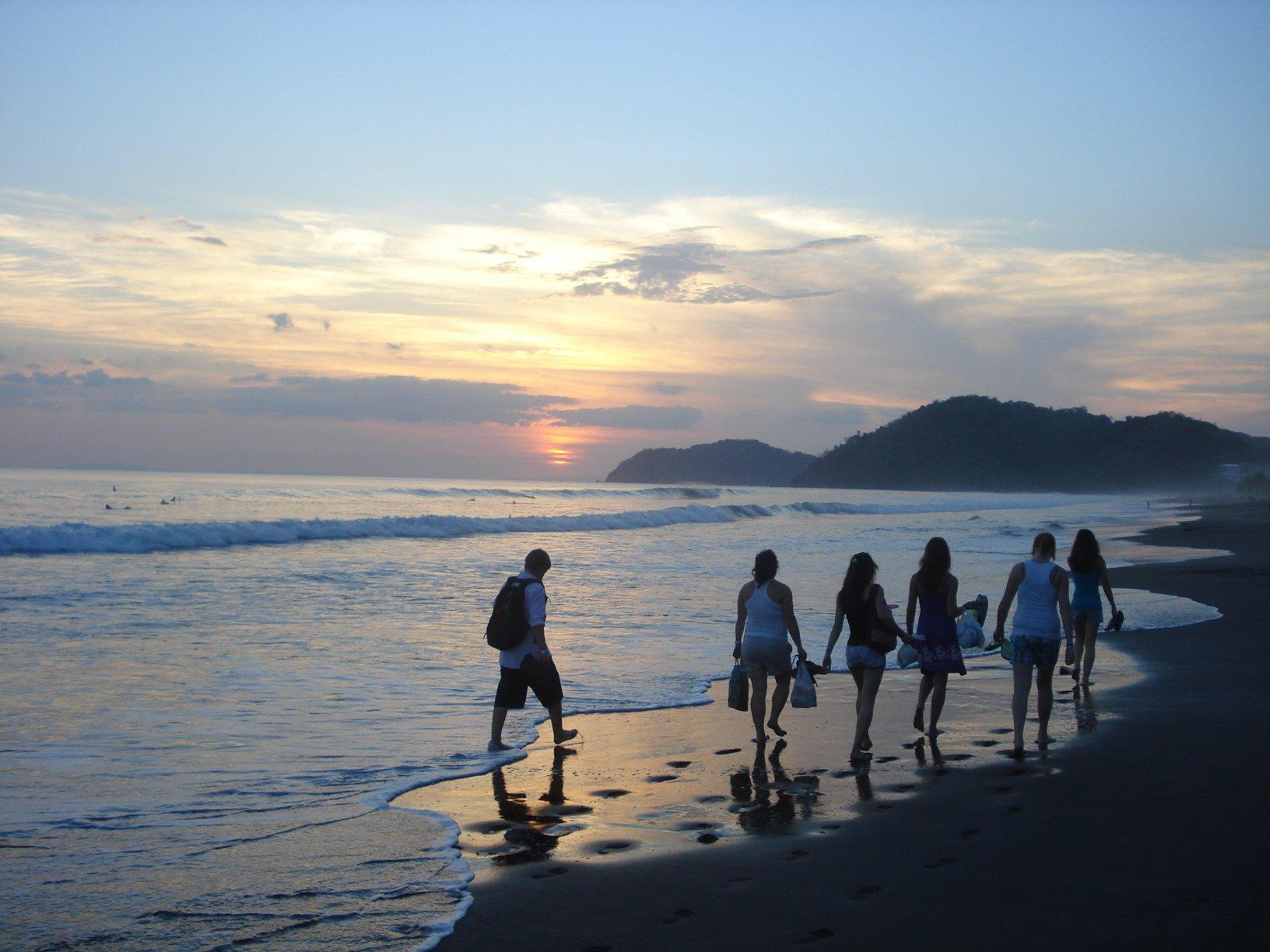 Jeunes marchant sur la plage au coucher du soleil