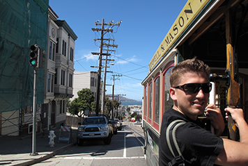 Étudiant sautant dans un tramway à San Francisco