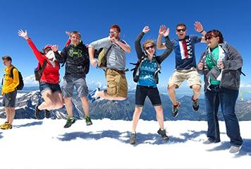 Jeunes sautant devant un paysage de montagnes
