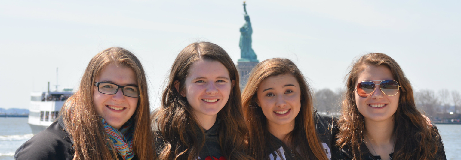 Smiling students in front of Liberty Statue