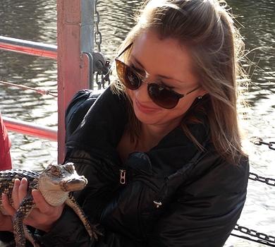 Jeune fille qui porte un bébé alligator